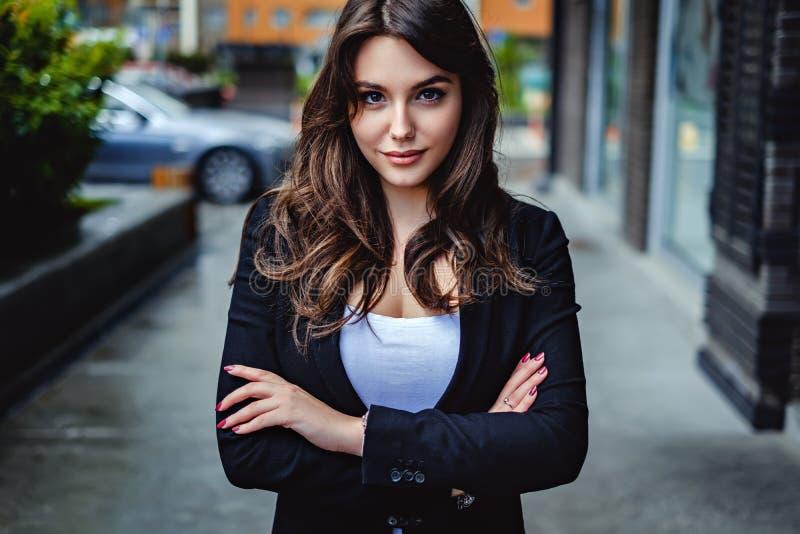 Überzeugte Geschäftsfrau, welche die Kamera betrachtet stockfoto