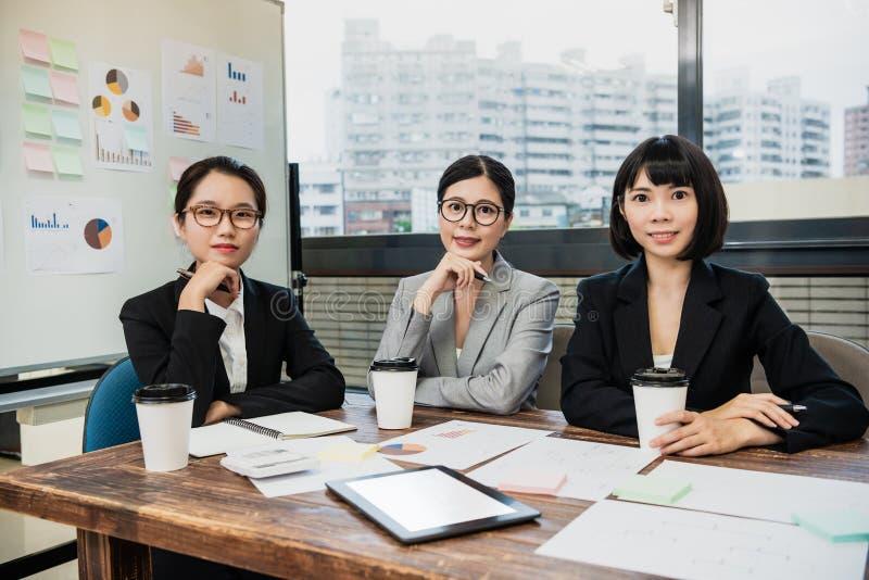 Überzeugte Geschäftsfrauen, die am Schreibtisch sitzen stockfotografie