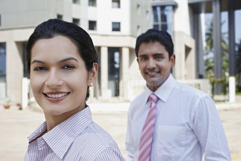 Überzeugte Geschäftsleute, die äußeres Gebäude stehen stockbild
