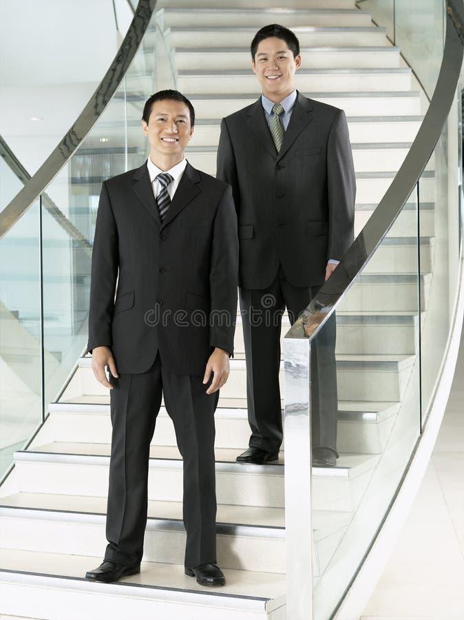Überzeugte Geschäftsmänner, die auf Treppe stehen stockfotos