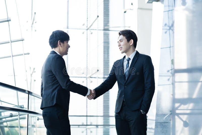 Überzeugte Geschäftsmänner, die Hände und das Lächeln rütteln stockfotos