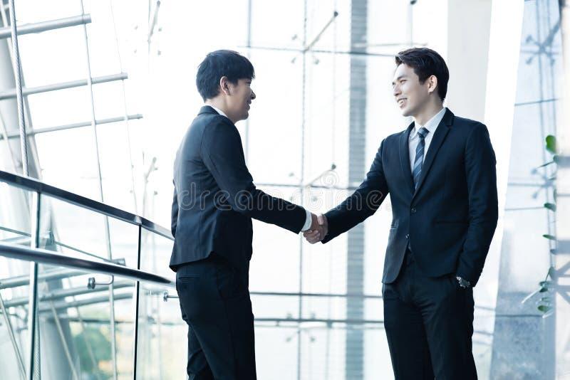 Überzeugte Geschäftsmänner, die Hände und das Lächeln rütteln stockbild