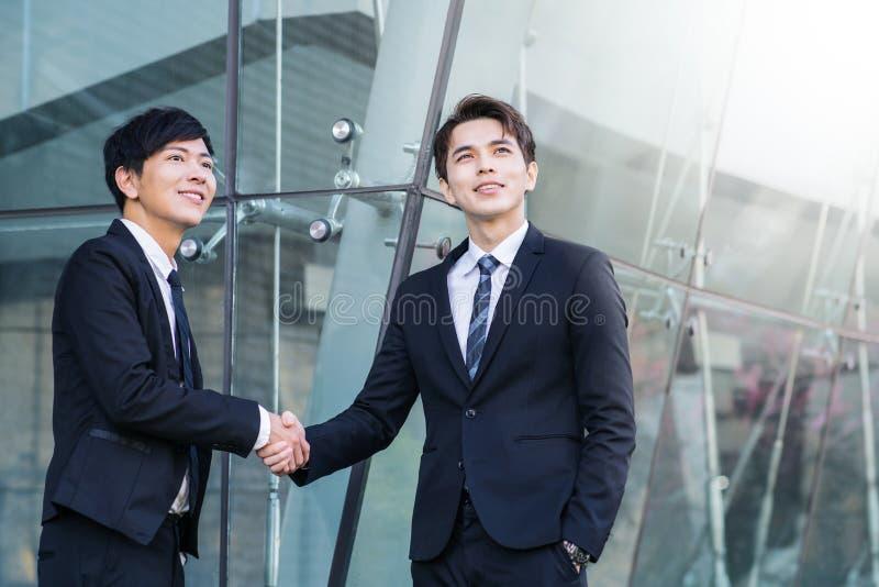 Überzeugte Geschäftsmänner, die Hände und das Lächeln rütteln lizenzfreies stockfoto