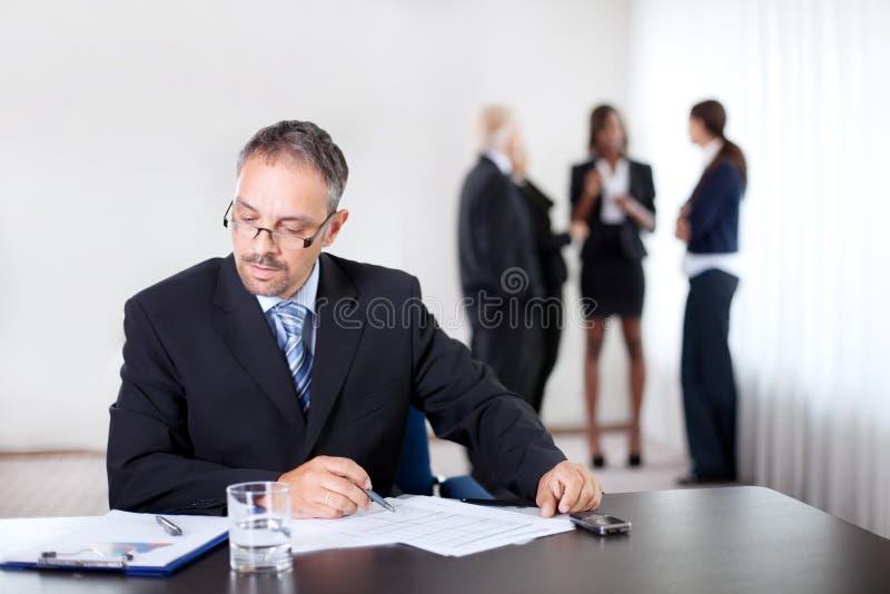 Überzeugte Geschäftsmannlesung und -schreiben stockbild