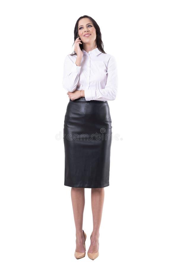 Überzeugte glückliche junge attraktive Geschäftsfrau, die am Telefon weg lächelt und schaut spricht stockfoto