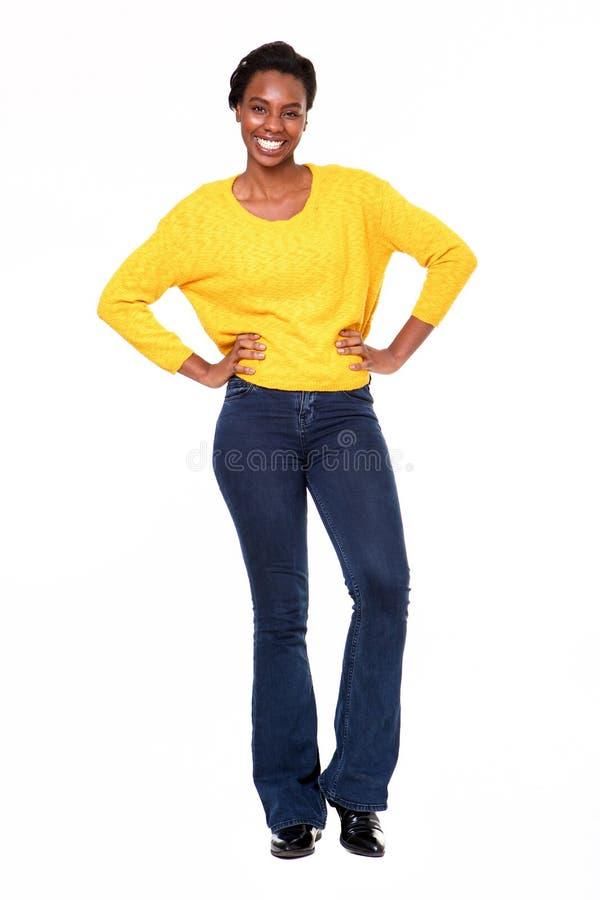 Überzeugte glückliche schwarze Frau des vollen Körpers, die auf weißem Hintergrund steht lizenzfreie stockfotografie