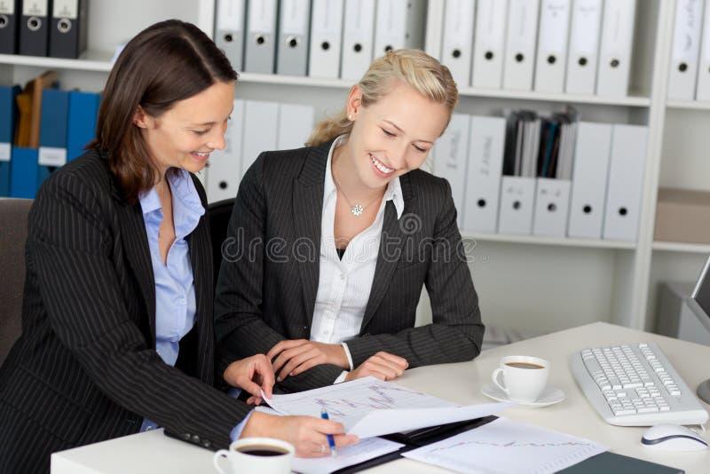 Überzeugte junge Geschäftsfrauen, die am Schreibtisch sitzen lizenzfreie stockfotografie