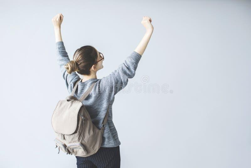 Überzeugte junge Studentin hob oben Arme mit Rucksack an lizenzfreie stockfotos