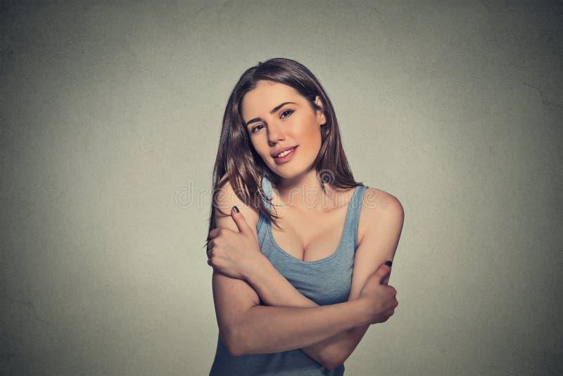 Überzeugte lächelnde Frau, die das Umarmen hält lizenzfreie stockfotografie