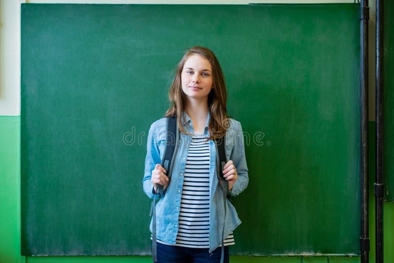 Überzeugte lächelnde weibliche hohe Schülerstellung vor Tafel im Klassenzimmer, tragender Rucksack, Kamera betrachtend stockfotografie