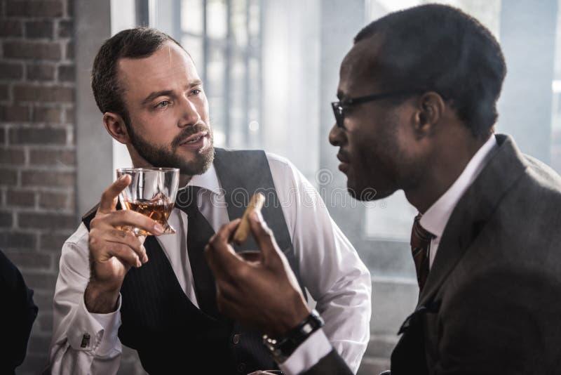 Überzeugte Männer mit Zigarre und Glas Alkoholgetränkeunterhaltung stockfoto