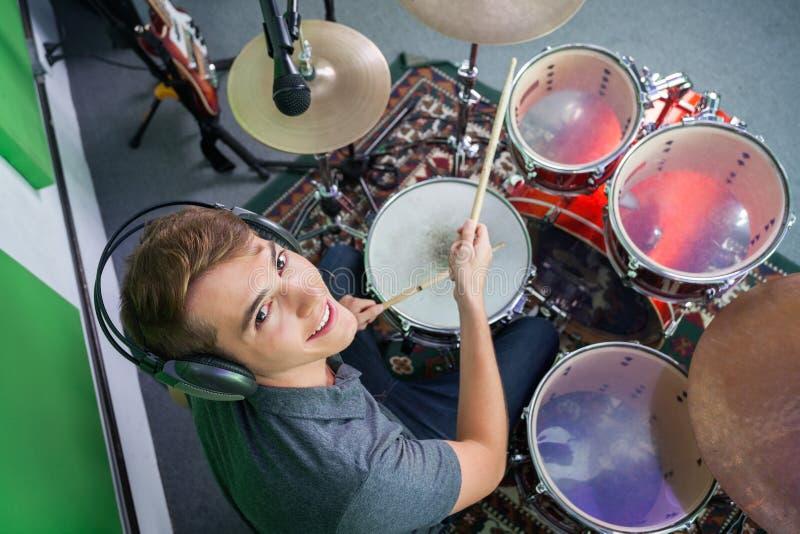 Überzeugte männliche Schlagzeuger-Wearing Headphones While-Ausführung stockbilder