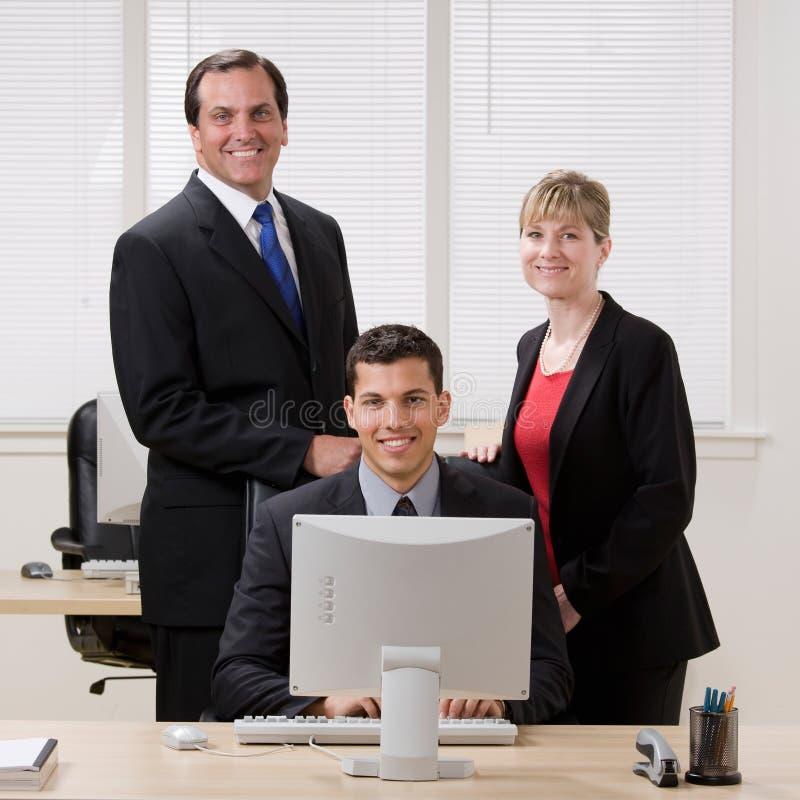 Überzeugte Mitarbeiter, die am Schreibtisch stehen stockbilder