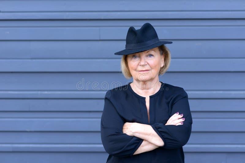Überzeugte modische ältere Dame in einem stilvollen Hut stockfotos