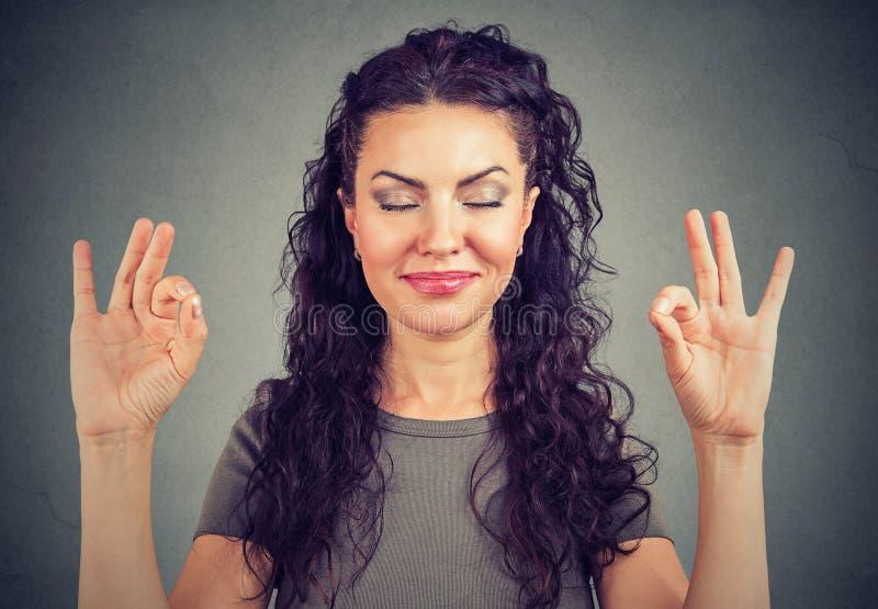 Überzeugte nette junge Frau, die glücklich meditiert lizenzfreies stockbild