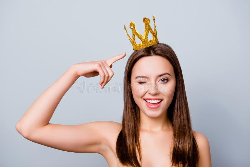 Überzeugte nette schöne junge Frau mit einer Krone auf ihrem Kopf ist stockbilder