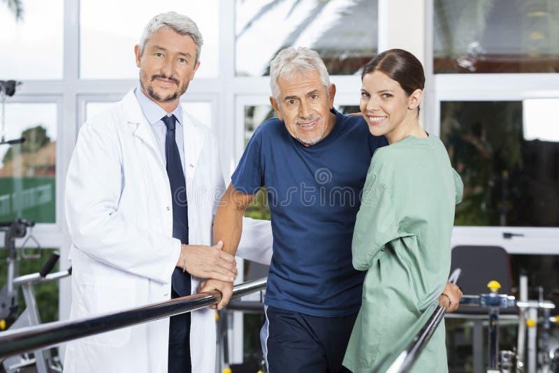 Überzeugte Physiotherapeuten mit älterem Patienten im Eignungs-Studio stockfotografie