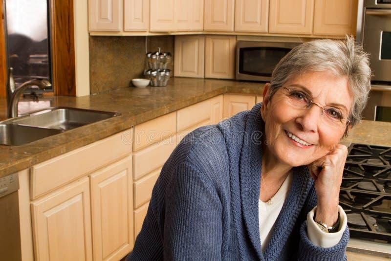 Überzeugte reife ältere Frau zu Hause lizenzfreie stockfotos
