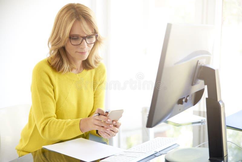 Überzeugte reife Geschäftsfrau, die Handy im Büro verwendet stockfoto