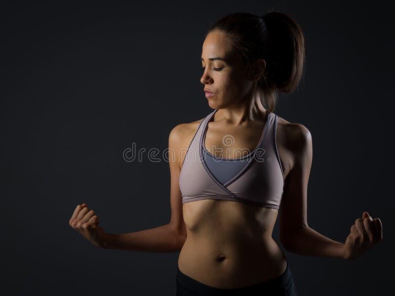 Überzeugte sexy Frau, die heraus ihr Bizeps überprüft stockfotografie