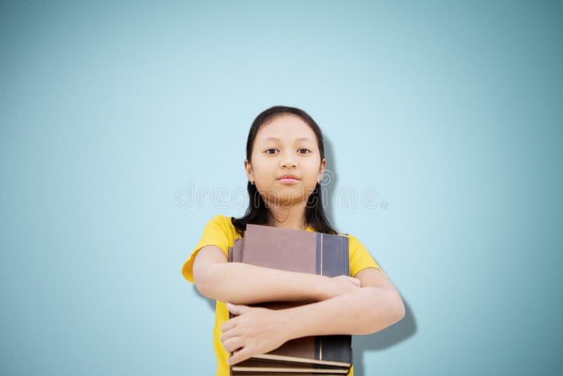 Überzeugte Studentin, die Bücher auf Studio hält stockbild