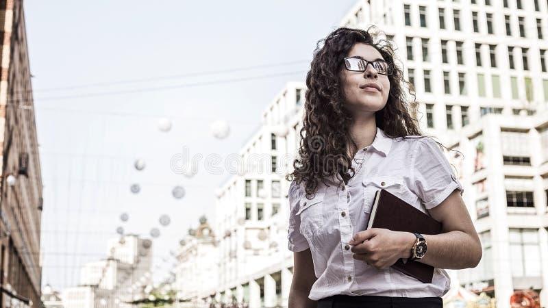 Überzeugte und recht junge Frau mit schwarzer Stellung des gelockten Haares auf dem Gebäudehintergrund stockfoto