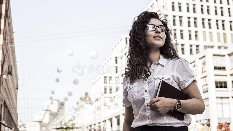 Überzeugte und recht junge Frau mit schwarzer Stellung des gelockten Haares auf dem Gebäudehintergrund stockfotos