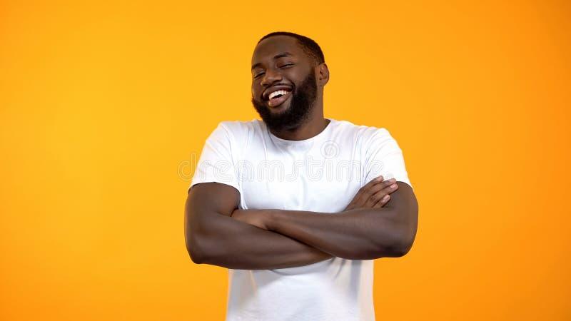 ?berzeugter afro-amerikanischer Mann, der mit den H?nden gekreuzt, lustige Geschichte lacht lizenzfreies stockfoto