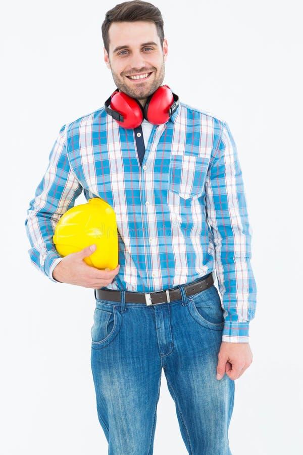 Überzeugter Arbeiter mit Hardhat- und Ohrmuffen lizenzfreie stockbilder