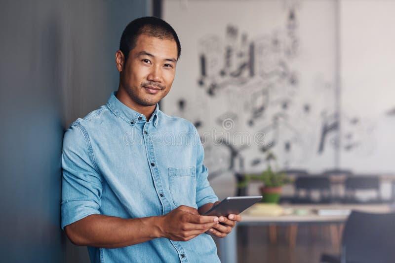 Überzeugter asiatischer Designer, der eine Tablette in einem modernen Büro verwendet stockbild