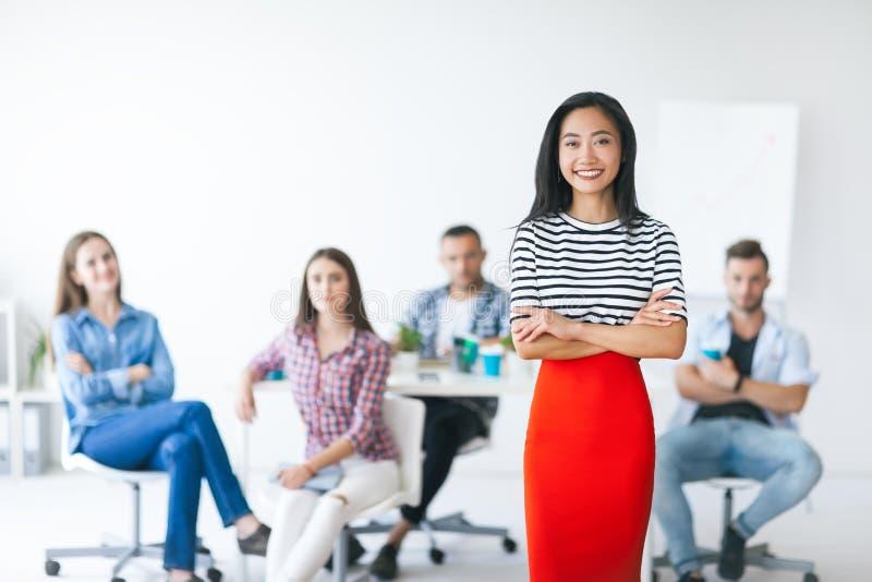 Überzeugter asiatischer führender Vertreter der Wirtschaft mit ihrem Team auf Hintergrund stockfoto