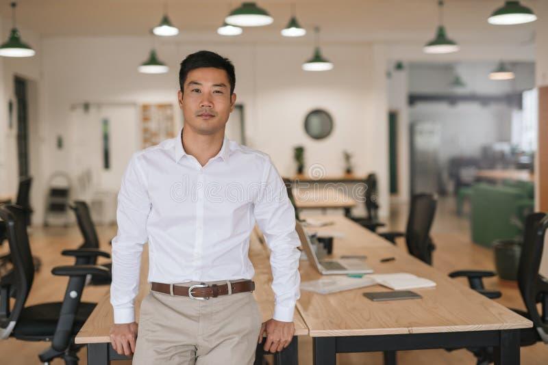 Überzeugter asiatischer Geschäftsmann, der auf einem Schreibtisch in einem Büro sich lehnt stockbilder