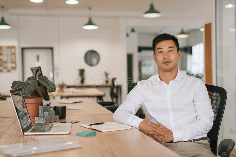 Überzeugter asiatischer Geschäftsmann, der an seinem Schreibtisch arbeitet lizenzfreie stockfotografie
