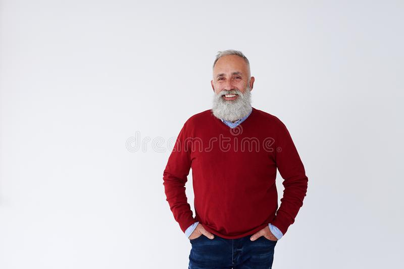 Überzeugter bärtiger reifer Mann mit den Händen in den Taschen, die Ca betrachten stockfoto