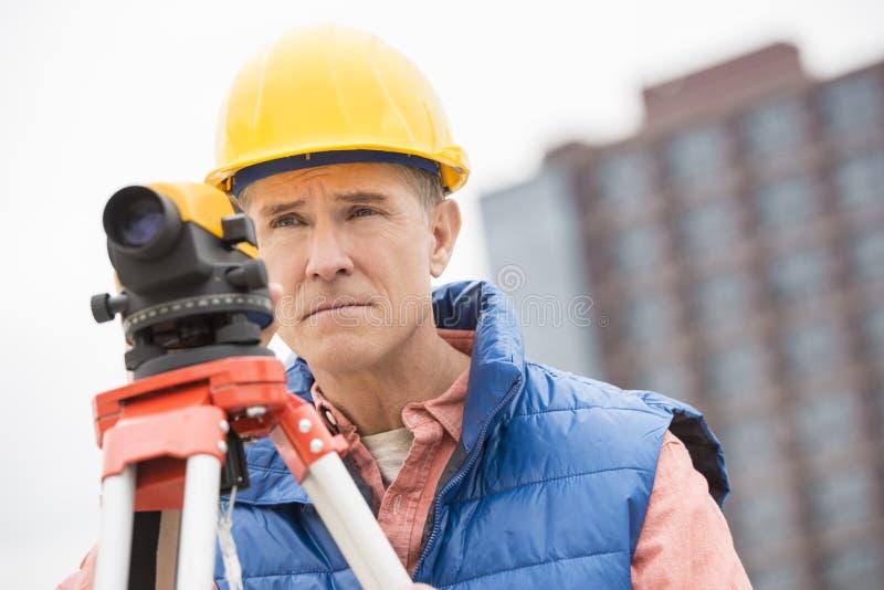 Überzeugter Bauarbeiter With Theodolite Looking weg stockbilder
