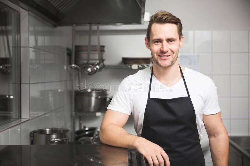 Überzeugter Chef, der in der Küche steht lizenzfreie stockfotos