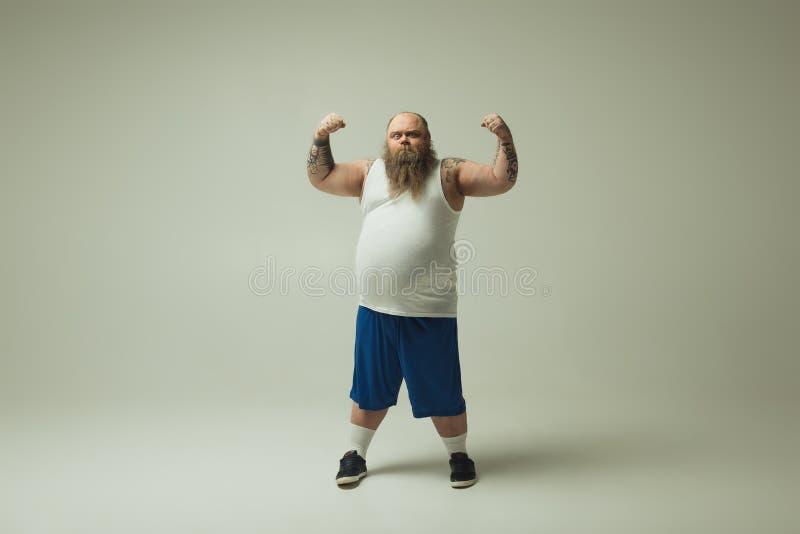 Überzeugter dicker Mann, der seine Muskeln belastet lizenzfreies stockfoto