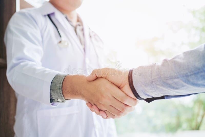 Überzeugter Doktor, der Hände mit Patienten rüttelt, sprechen im hospit lizenzfreie stockfotos