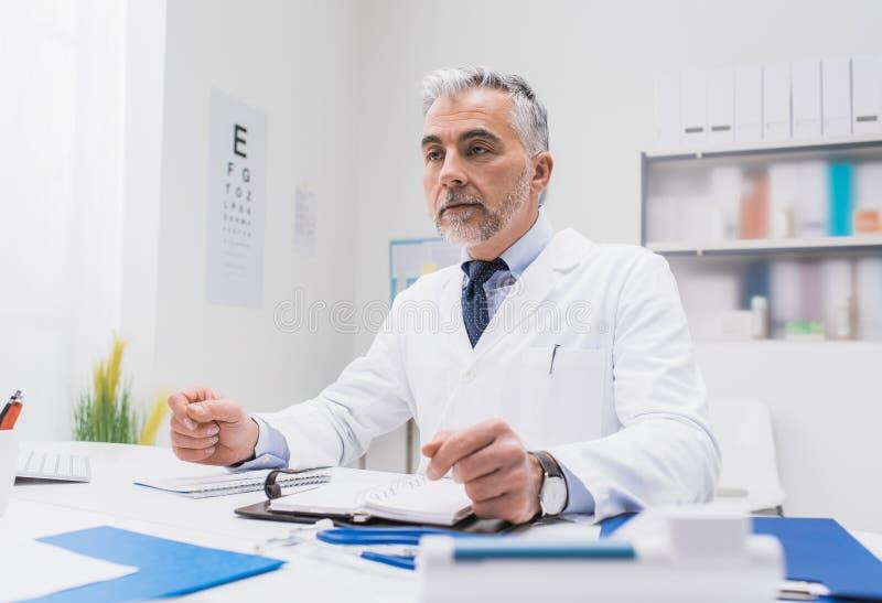 Überzeugter Doktor, der am Schreibtisch sitzt stockbilder