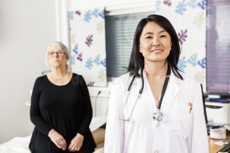 Überzeugter Doktor Smiling While Patient, das im Hintergrund sitzt stockfotos