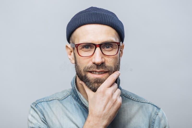 Überzeugter erfüllter bärtiger Mann hält Hand auf Kinn, hört aufmerksam Gesprächspartner, trägt die moderne Kleidung, lokalisiert stockfoto