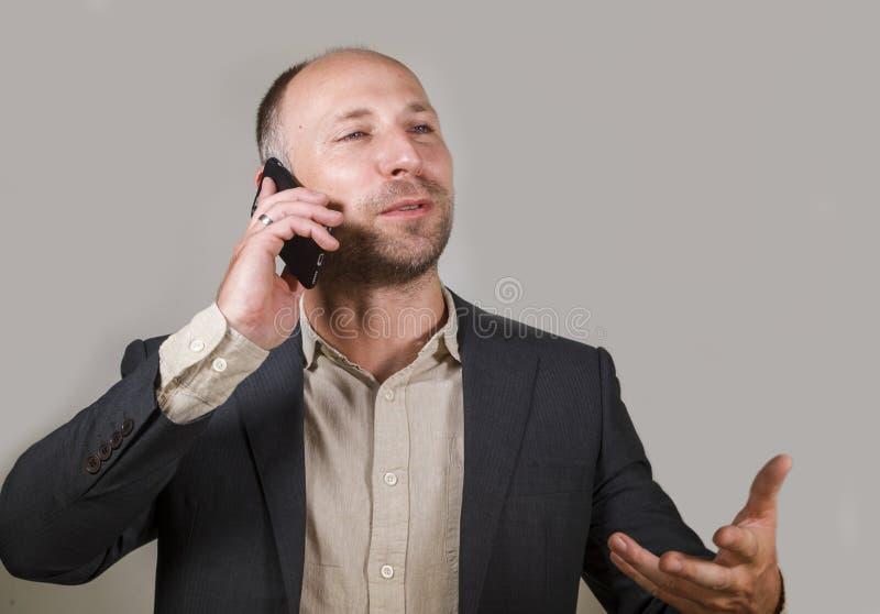 Überzeugter erfolgreicher Geschäftsmann, der am Handy hat Geschäftsgespräch mit dem Mobiltelefonlächeln nett in Unternehmens spri stockbilder