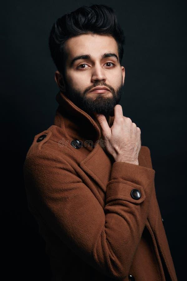 Überzeugter erfolgreicher Geschäftsmann im braunen Mantel stockfotos