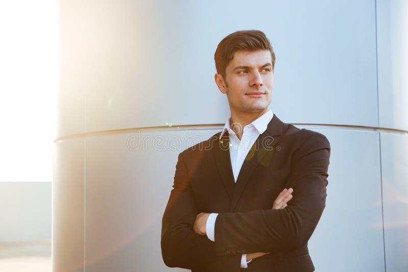 Überzeugter erfolgreicher junger Geschäftsmann, der mit den Armen gekreuzt steht stockfotos