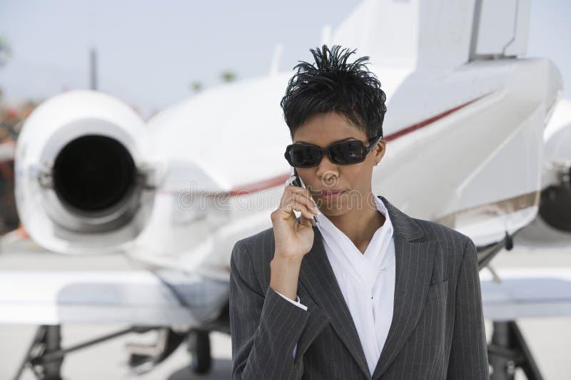 Überzeugter Geschäftsfrau-Using Cellphone At-Flugplatz lizenzfreies stockfoto