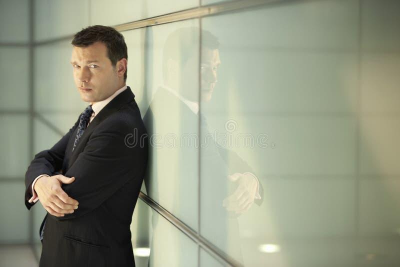 Überzeugter Geschäftsmann With Arms Crossed, das auf Glaswand sich lehnt stockfotografie