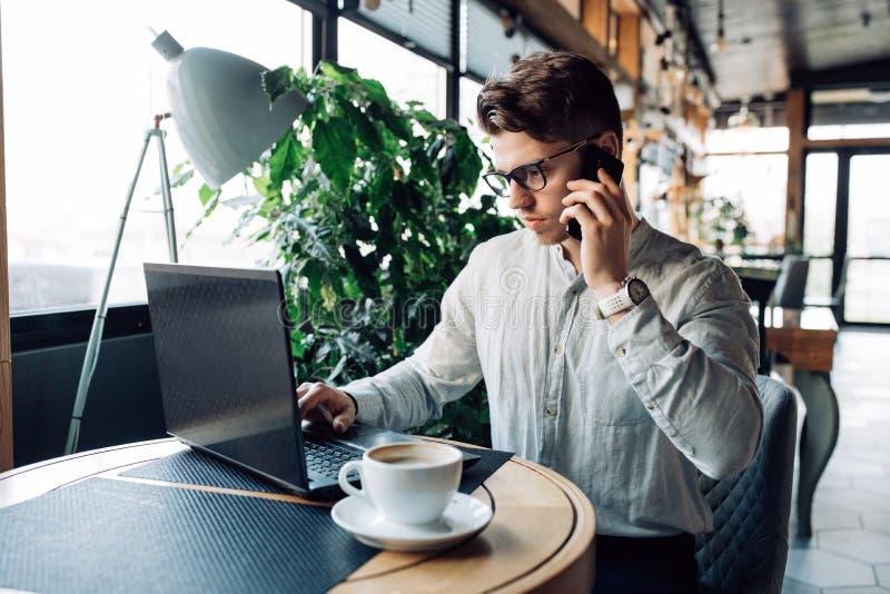 Überzeugter Geschäftsmann, der auf Smartphone beim Sitzen am Café mit Laptop spricht stockfoto