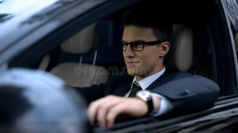Überzeugter Geschäftsmann, der das erstklassige Klassenauto, zufriedengestellt mit neuem gekauftem Auto fährt lizenzfreie stockbilder