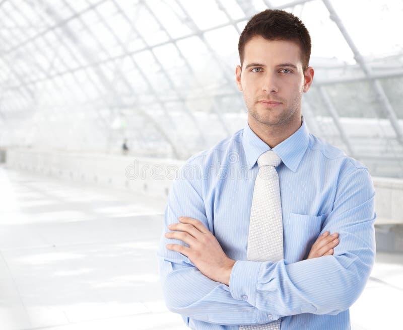 Überzeugter Geschäftsmann, der an der modernen Durchführung steht stockfotos