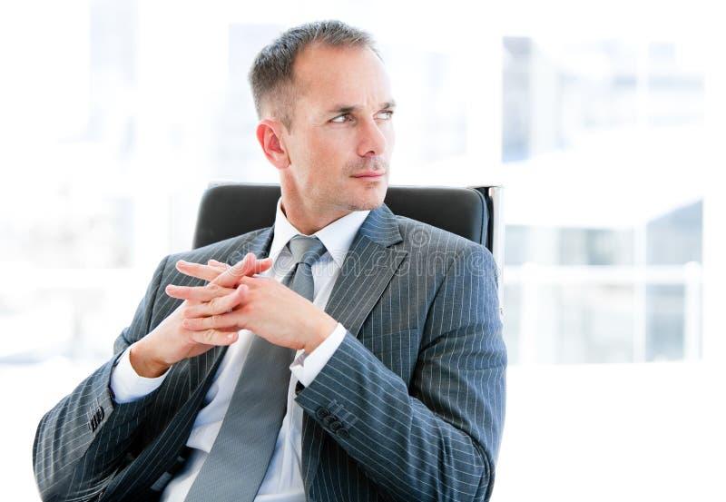 Überzeugter Geschäftsmann, der an die Firma denkt lizenzfreie stockbilder